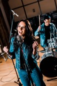 selective focus of beautiful emotional woman singing while mixed race musician playing drums in recording studio