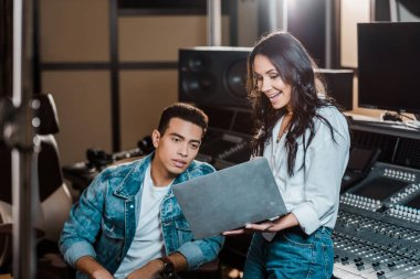 beautiful sound producer using laptop near mixed race friend in recording studio