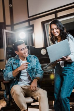 cheerful multicultural sound producers using laptop in recording studio
