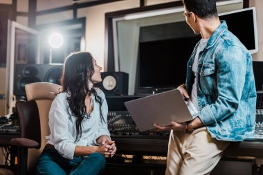 two multicultural sound producers working in recording studio together