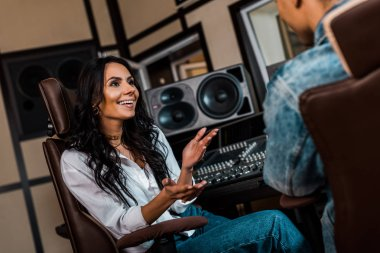 cheerful attractive sound producer talking to mixed race colleague in recording studio