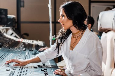 beautiful concentrated sound producer working at mixing console in recording studio