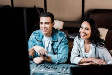 two cheerful multicultural sound producers working at mixing console in recording studio