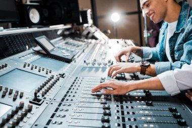 Cropped view of woman working at mixing console with mixed race colleague in recording studio stock vector