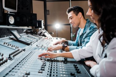 Two young multicultural sound producers working at mixing console i recording studio stock vector
