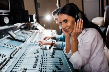 Sound producer in headphones near mixed racial friend working at mixing console stock vector