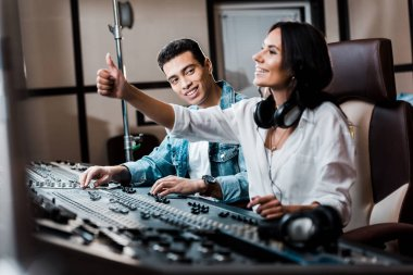 selective focus of cheerful sound produce showing thumb up while working at mixing console near smiling mixed race friend