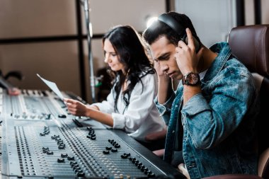 selective focus of handsome mixed race sound producer in earphones near pretty colleague working at mixing console