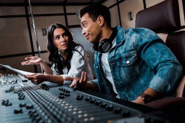 two quarrelling multicultural sound producers working at mixing console in recording studio