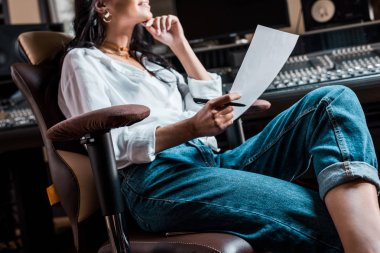 partial view of sound producer sitting in office chair near mixing console