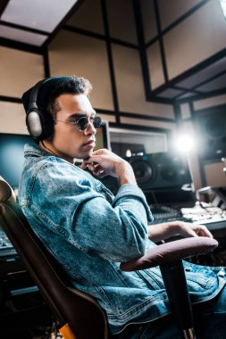 handsome serious mixed race sound producer in sunglasses and headphones sitting in recording studio