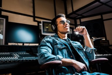 good-looking, mixed race sound producer in headphones listening music in recording studio