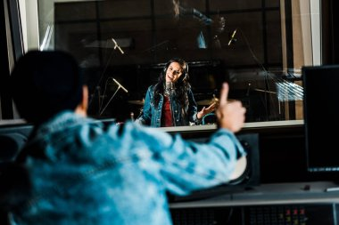 selective focus of mixed race sound producer showing thumb up to woman singing in recording studio