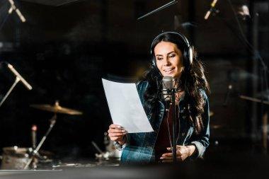 Beautiful woman in headphones singing in recording studio near microphone stock vector