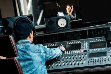 selective focus of mixed race sound producer working at mixing console while pretty woman singing in recording studio