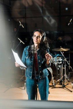 selective focus of inspired woman in headphones standing near microphone in recording studio
