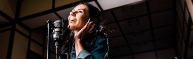 panoramic shot of beautiful inspired woman singing near microphone in recording studio