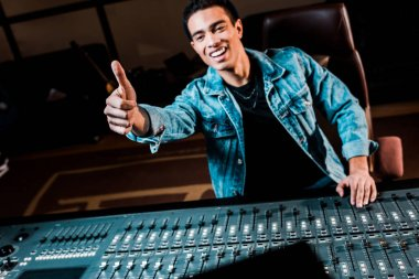 Smiling mixed race sound producer showing thumb up while standing near mixing console in recording studio stock vector