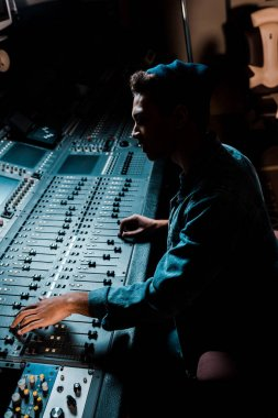 sound producer working at mixing console in dark recording studio