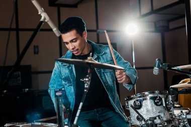handsome, inspired mixed race musician playing drums in recording studio