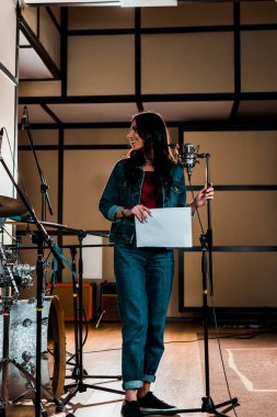 beautiful singer standing near microphone and holding paper with text in recording studio