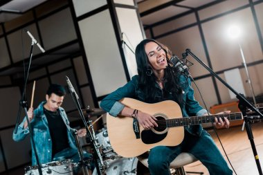 selective focus of beautiful inspired musician playing guitar and singing while mixed race man playing drums in recording studio