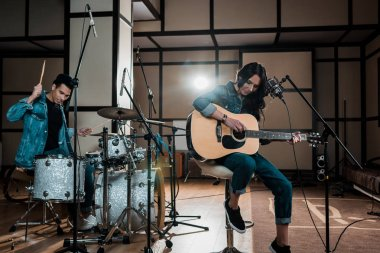 beautiful woman playing guitar while mixed race musician playing drums in recording studio