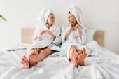 szelektív hangsúly a mezítlábas lányok fülbevaló, fürdőköpeny és törölköző a fejek az ágyban fekve, és nézi egymást