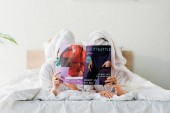 women in bathrobes and jewelry, with towels on heads hiding behind magazine together while lying in bed