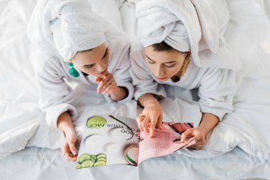 overhead view of stylish women in bathrobes, earrings and with towels on heads reading magazine together while lying in bed