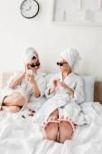 szelektív hangsúly a mezítláb nő a fürdőköpeny és napszemüveg fekvő pedikűr az ágyban
