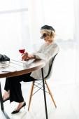 Elegantní blondýnka v černém baretu a sluneční brýle, které sedí u stolu se sklenkou červeného vína