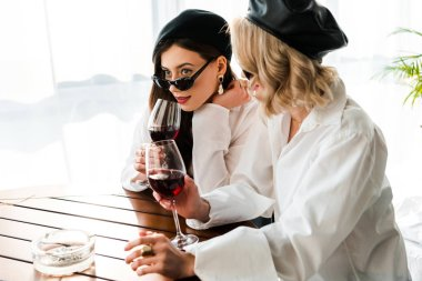 elegant brunette and blonde women in black berets and sunglasses drinking red wine at wooden table
