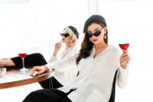 selective focus of elegant brunette woman in black beret and sunglasses with glass of red wine sitting near friend