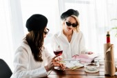 Fotografia brunette and blonde women in black berets and sunglasses drinking red wine and reading magazine