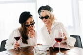 Fotografia brunette and blonde smiling women in black berets and sunglasses drinking red wine and reading magazine