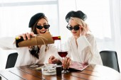 Fotografia brunette and blonde happy women in black berets and sunglasses pouring red wine and reading magazine