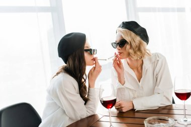 brunette and blonde women in black berets and sunglasses drinking red wine and smoking cigarettes