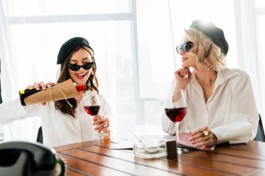brunette and blonde happy women in black berets and sunglasses pouring red wine