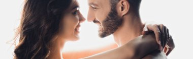 panoramic shot of nude smiling couple embracing isolated on white