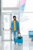 usmívající se šťastný Afroameričan muž chození s kufříkem v čekárně na letišti