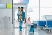 smiling african american father walking with happy children and baggage along waiting hall in airport
