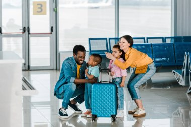 Smiling african american family with baggage and kids in airport stock vector