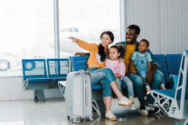Smiling african american family with baggage and kids sitting in airport while mother pointing with finger away stock vector