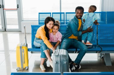 cheerful african american family with travel bags and kids sitting in airport