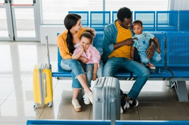 Cheerful african american family with travel bags and kids sitting in airport in waiting hall stock vector