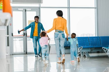mother with children walking to happy african american man in airport