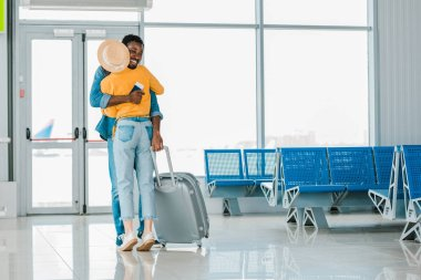 Happy african american man with travel bag hugging girlfriend in airport stock vector