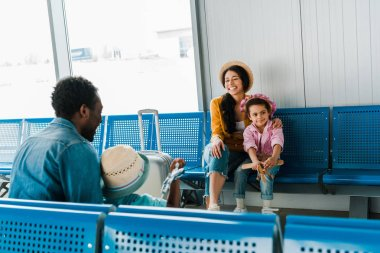smiling african american family sitting in airport and waiting for flight