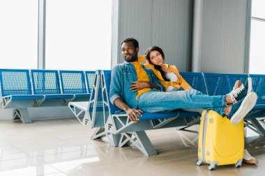 Tired african american couple sitting in departure lounge with suitcase and waiting for flight stock vector
